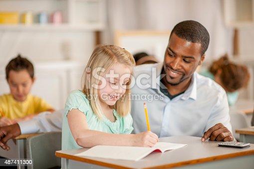 istock Teacher Helping Little Girl 487411300