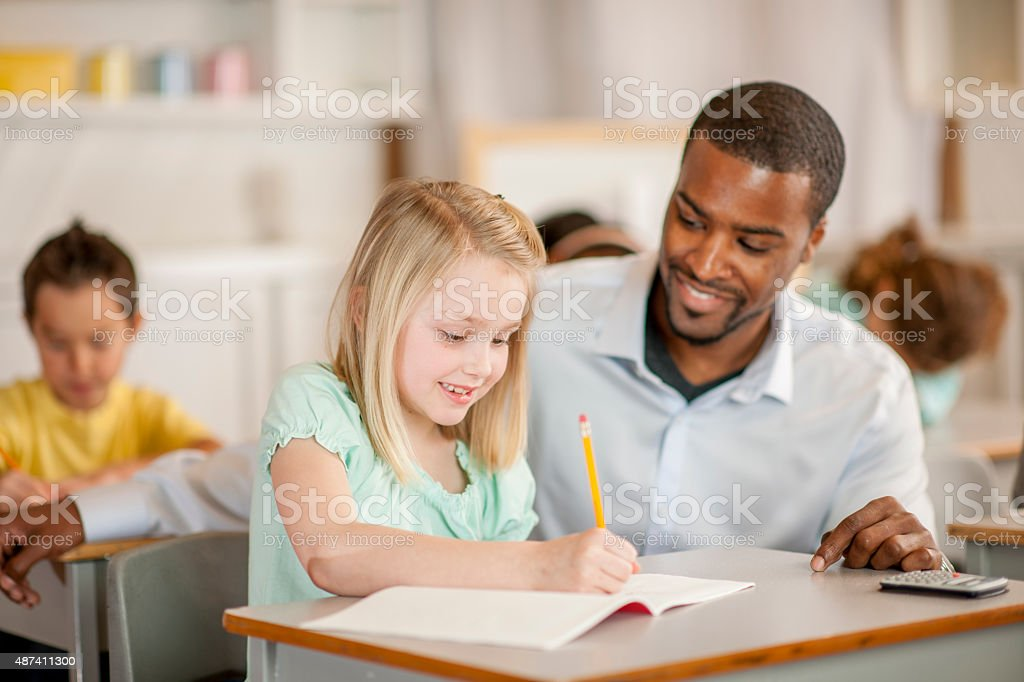 Teacher Helping Little Girl stock photo