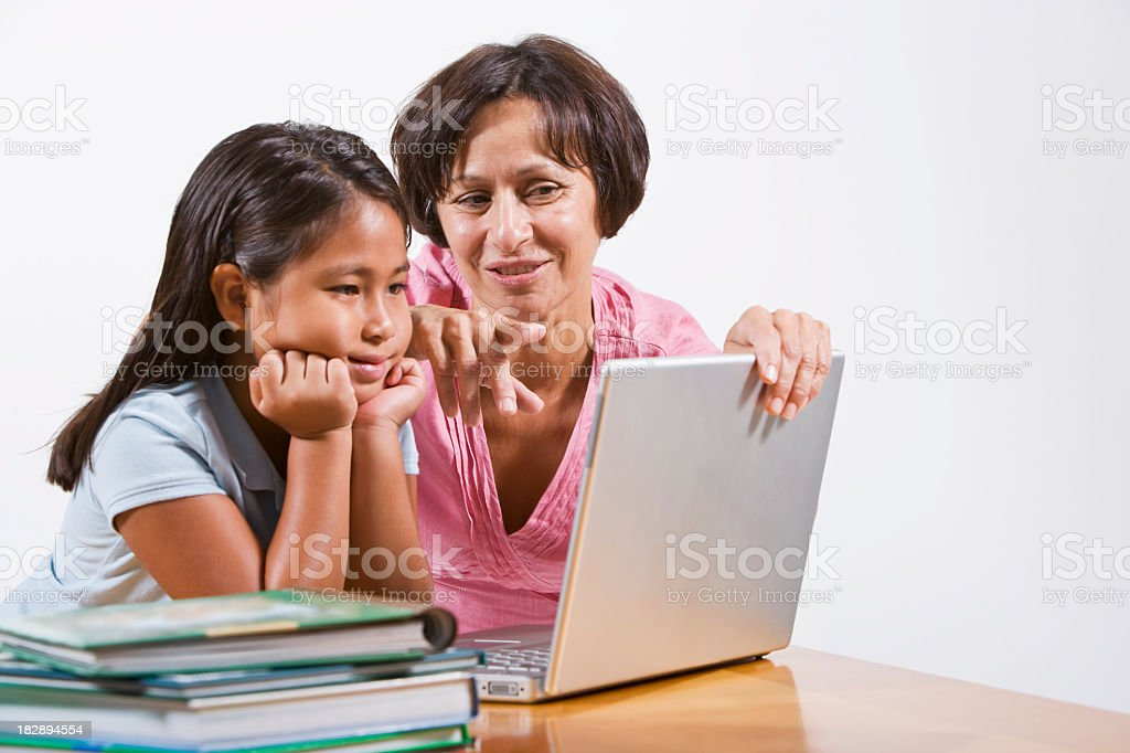 Teacher helping little girls with laptop computer royalty-free stock photo