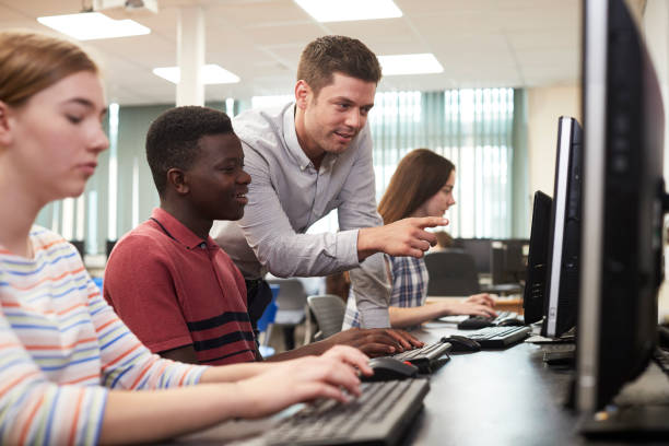 teacher helping male high school student working in computer class - high school teacher stock pictures, royalty-free photos & images