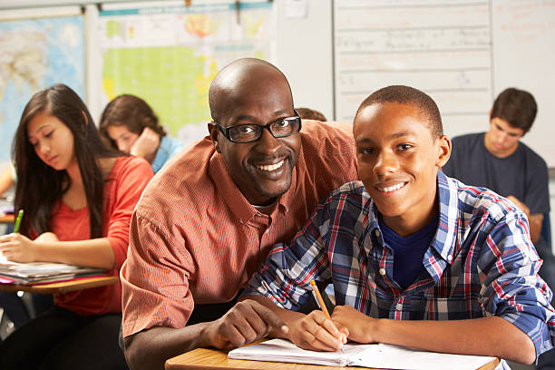 Teacher helping male pupil study at his desk in classroom stock photo