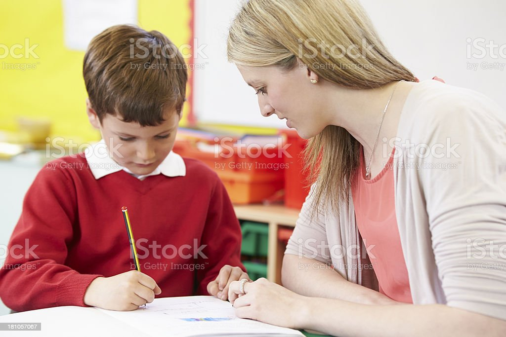 Teacher Helping Male Pupil With Practising Writing At Desk royalty-free stock photo