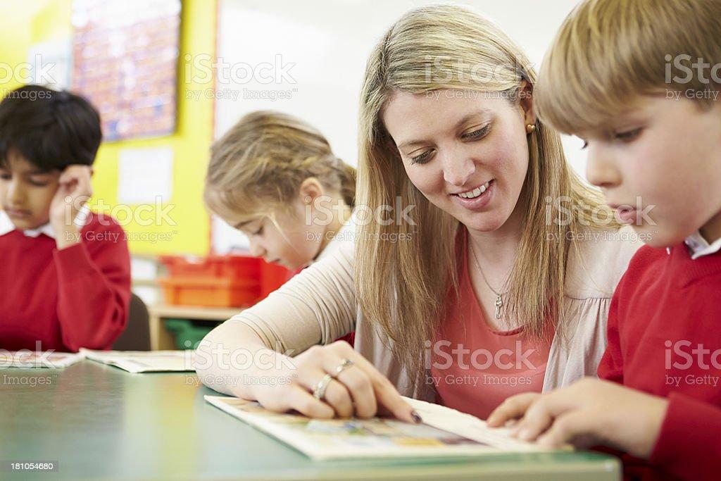 Enseignant aidant m le élève lecture au bureau pour travailler