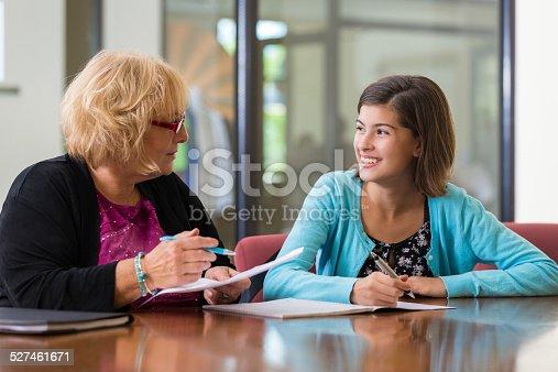 641755828 istock photo Teacher helping preteen student during after school tutoring program 527461671