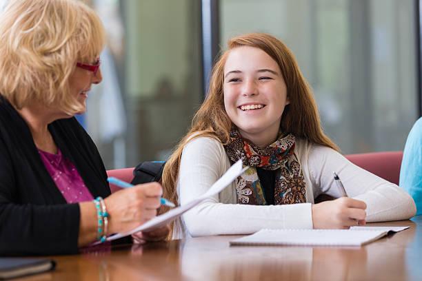 教師 preteen 学生のように宿題 tutoring セッション中 - 学校カウンセラー ストックフォトと画像