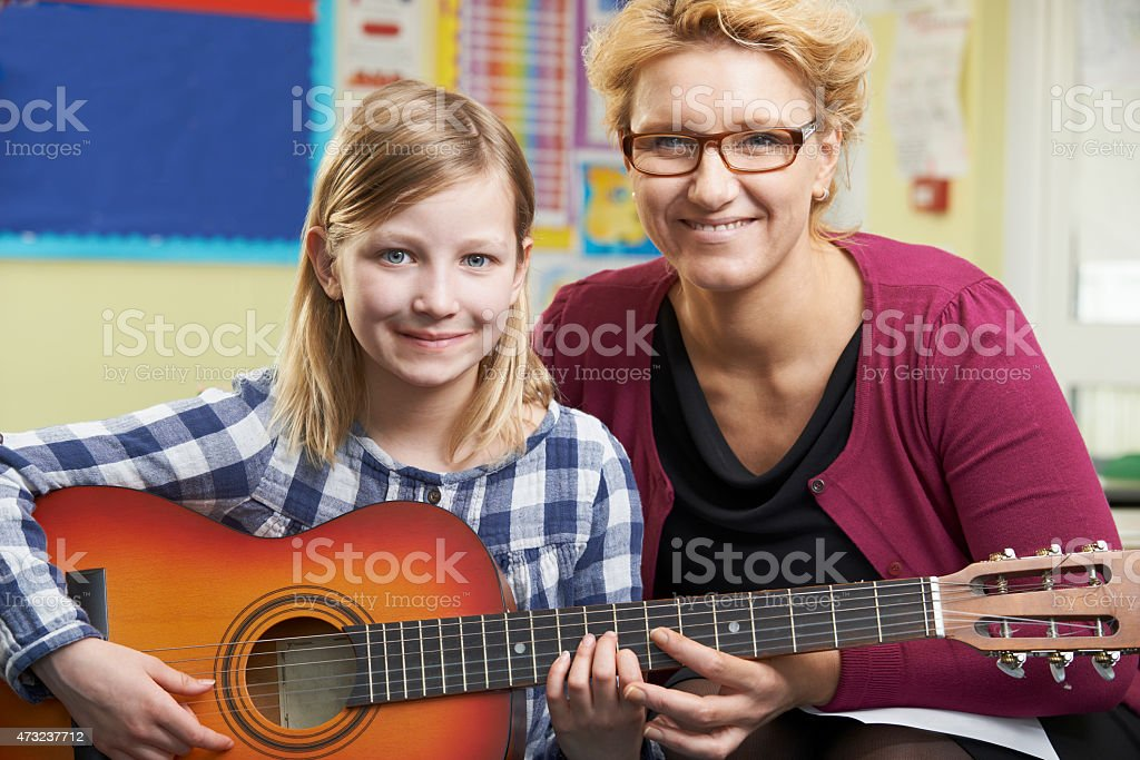 Teacher Helping Pupil To Play Guitar In Music Lesson stock photo