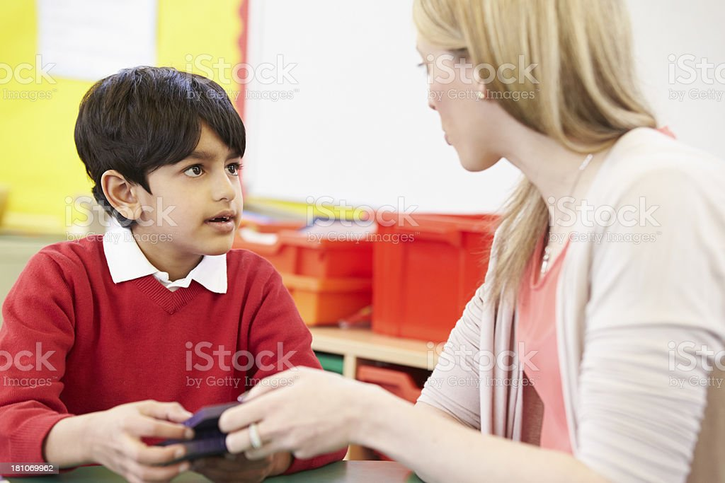 Teacher Helping Pupil With Maths At Desk royalty-free stock photo