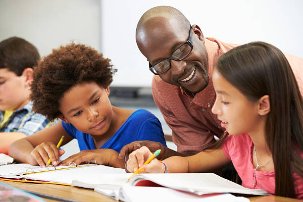 Teacher helping pupils study in the classroom Teacher Helping Pupils Studying At Desks In Classroom Checking Work Smiling elementary age stock pictures, royalty-free photos & images