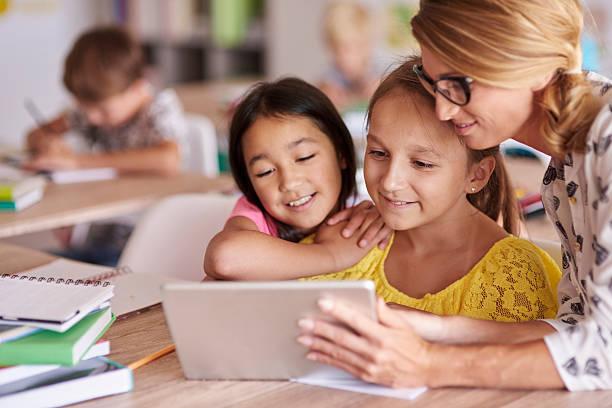 Teacher helping pupils with digital tablet - foto de acervo