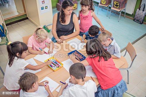 istock Teacher helping school children in drawing at desk 816391414