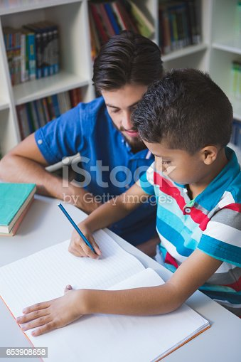 istock Teacher helping school kid with his homework in library 653908658