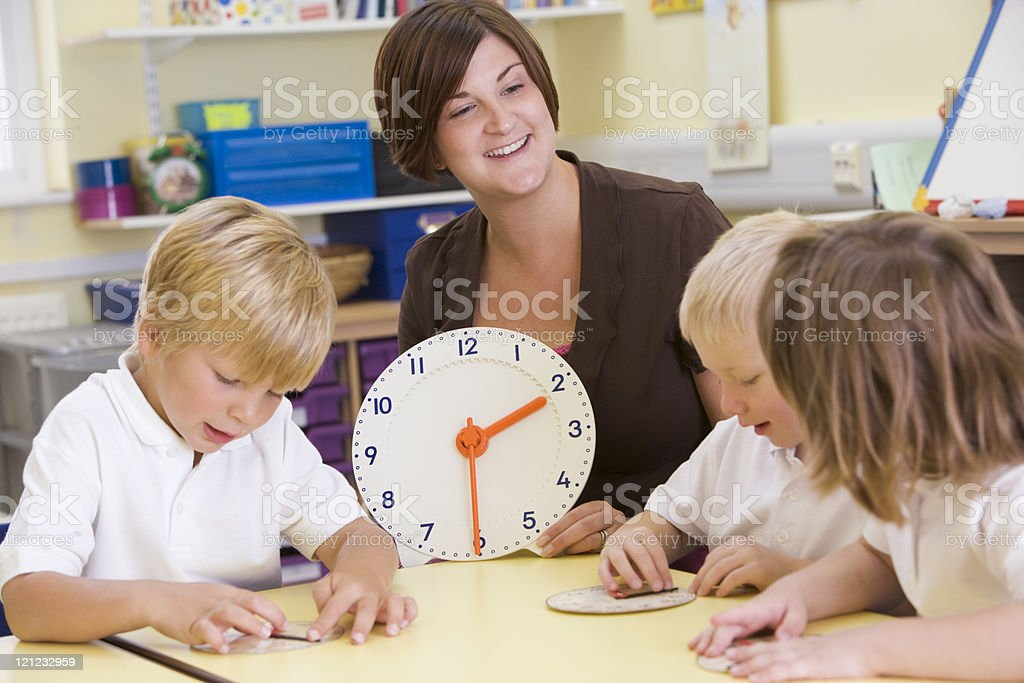 Teacher helping schoolchildren to tell time in primary school royalty-free stock photo
