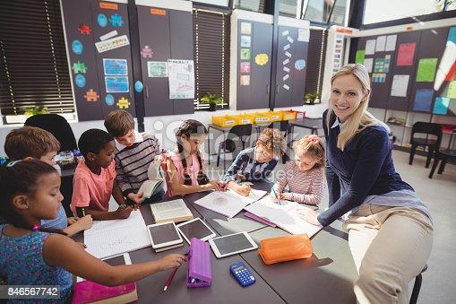 istock Teacher helping schoolgirl with her homework in classroom 846567742