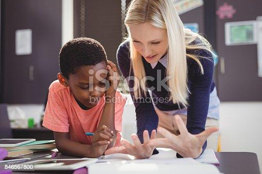 istock Teacher helping schoolgirl with her homework in classroom 846567800