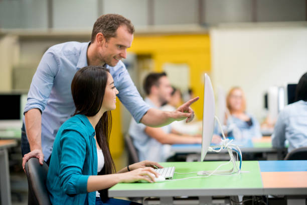 teacher helping student at an it class - professor stock photos and pictures