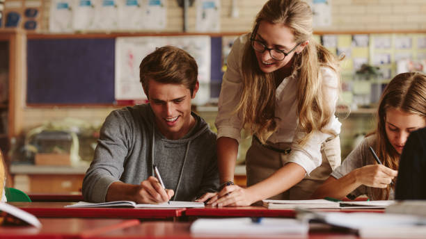 teacher helping student during her class - high school teacher stock pictures, royalty-free photos & images