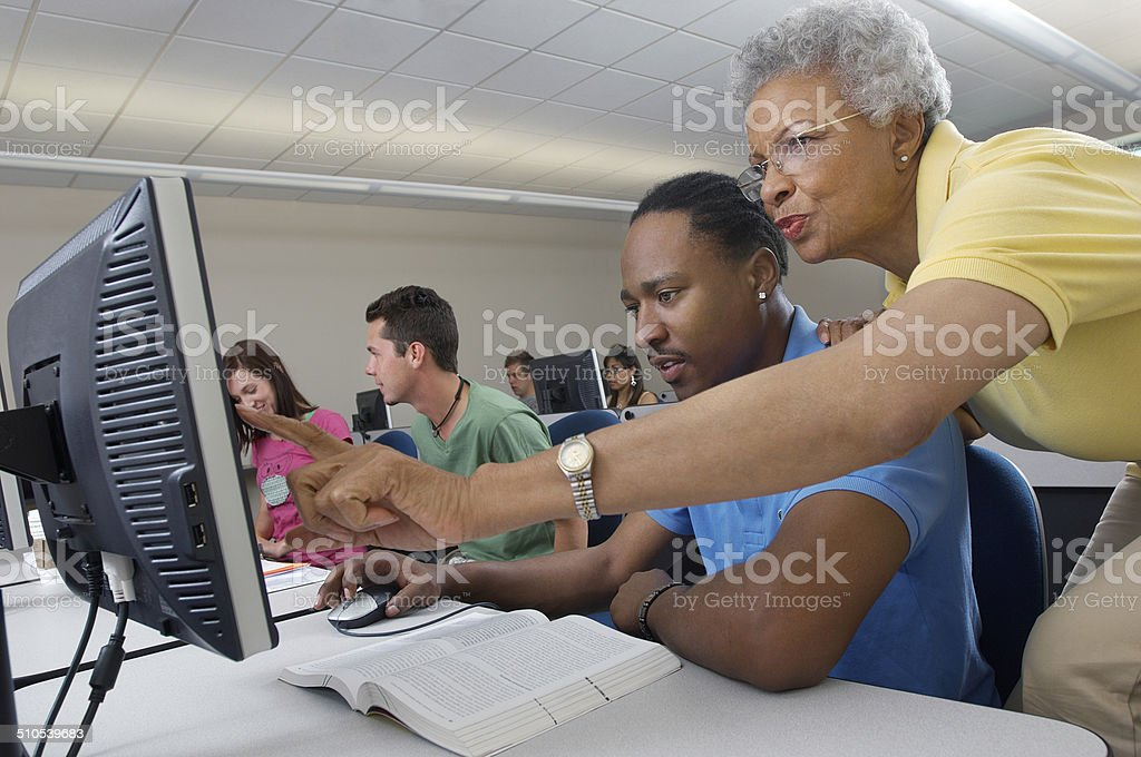 Teacher helping student in computer class royalty-free stock photo