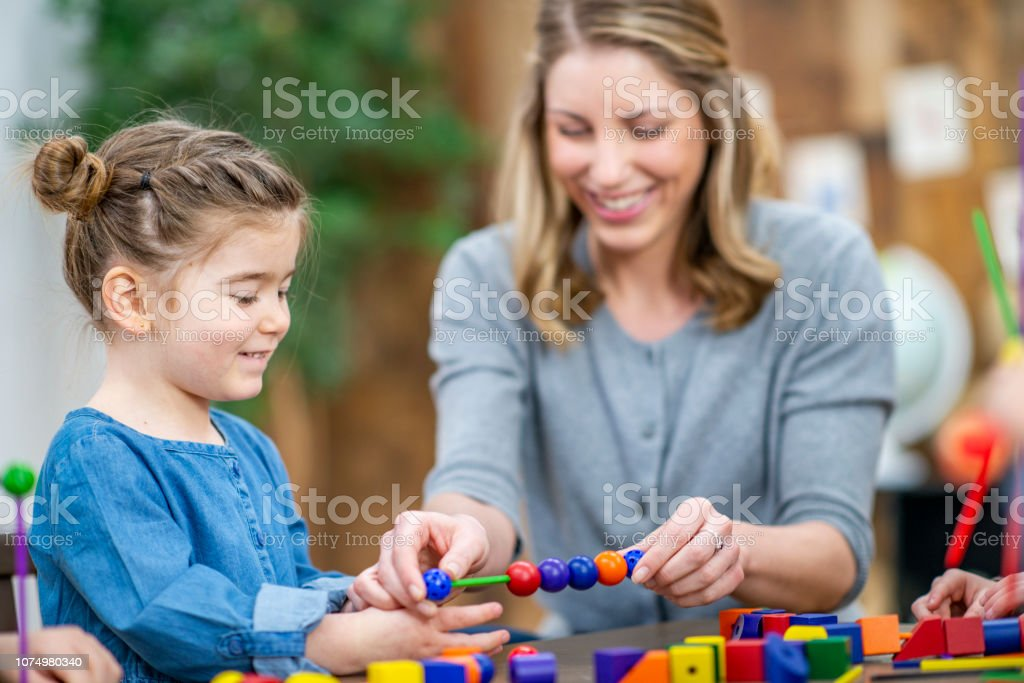 A cute little girl smiles as she strings beads with her teacher. Her...