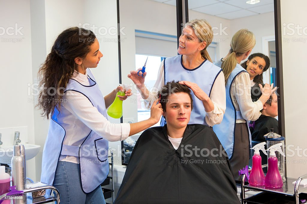 Teacher Helping Student Training To Become Hairdressers stock photo