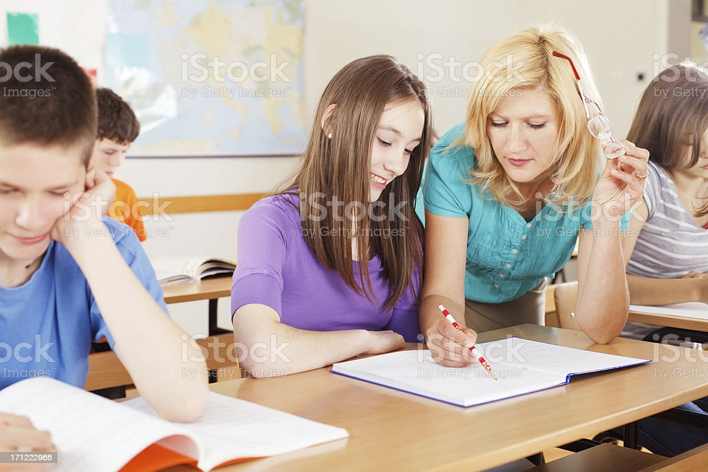 Teacher helping student with the school work. royalty-free stock photo