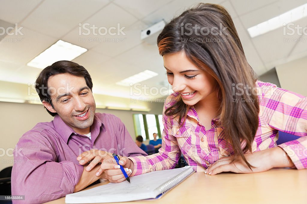 Teacher helping student with work in class royalty-free stock photo