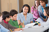 istock Teacher helping students in classroom 483621299