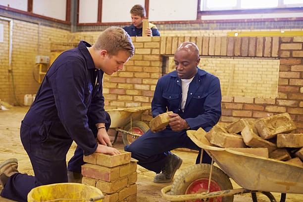 Teacher Helping Students Training To Be Builders stock photo