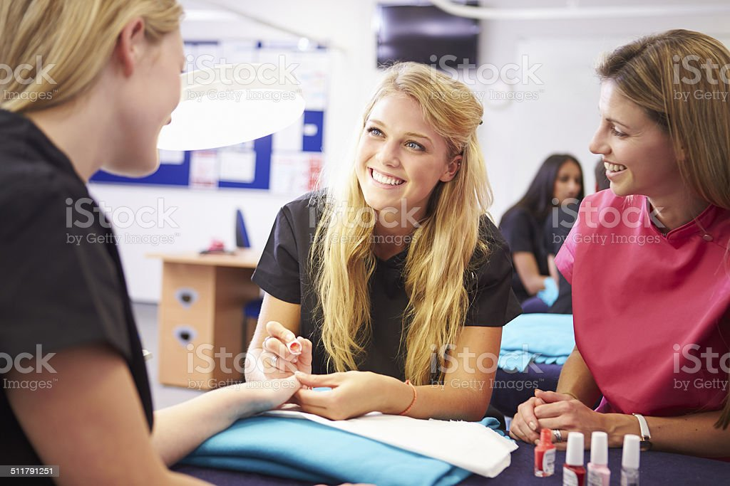 Teacher Helping Students Training To Become Beauticians stock photo