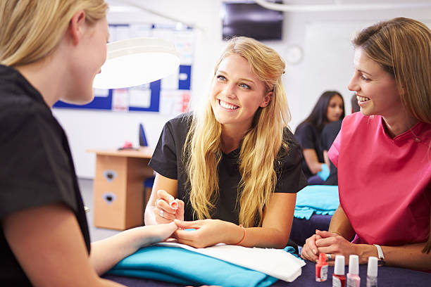 teacher helping students training to become beauticians - beautician stock photos and pictures