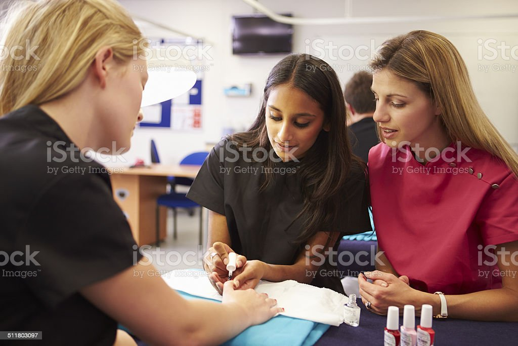 Teacher Helping Students Training To Become Beauticians royalty-free stock photo