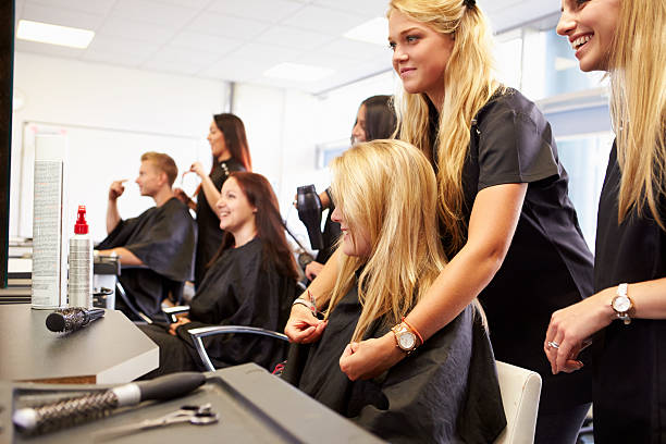 teacher helping students training to become hairdressers - beauty salon stock photos and pictures