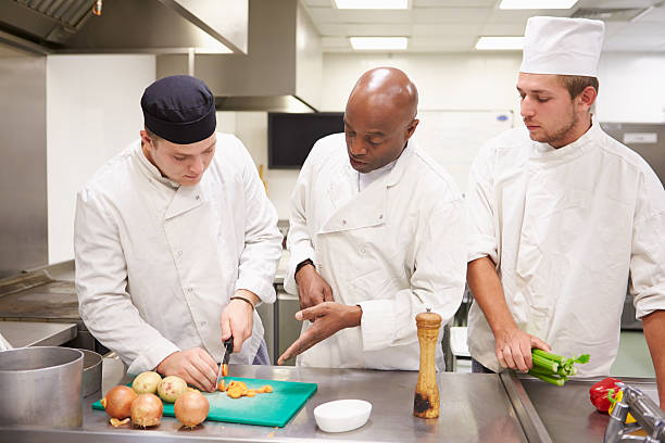 teacher helping students training to work in catering - food and drink stock photos and pictures