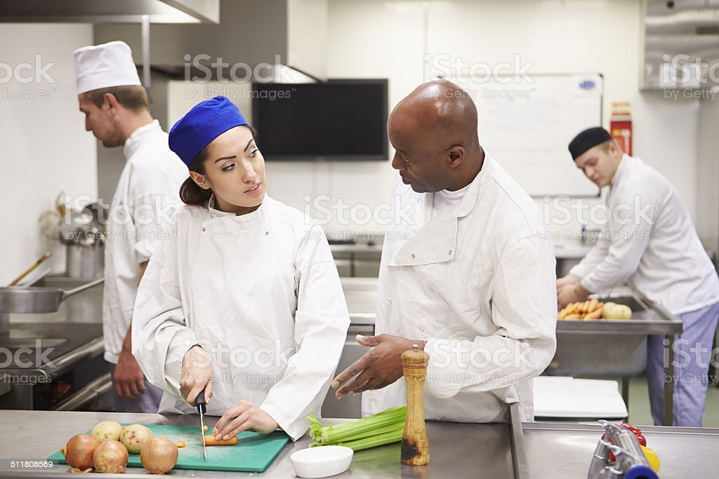 Teacher Helping Students Training To Work In Catering stock photo