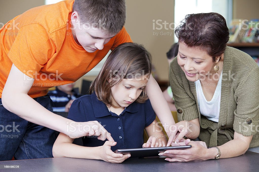 Teacher helping students with project on digital tablet royalty-free stock photo
