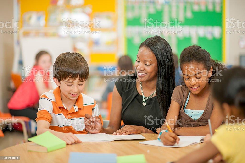 Profesor ayudando a los estudiantes con preguntas - foto de stock