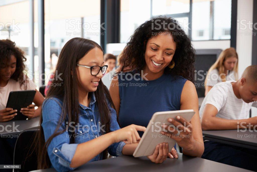 Teacher helping teenage schoolgirl with tablet computer stock photo
