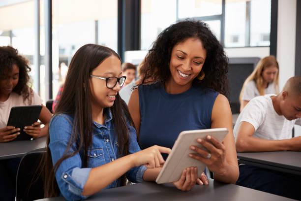 Professor, ajudando o estudante adolescente com computador tablet - foto de acervo