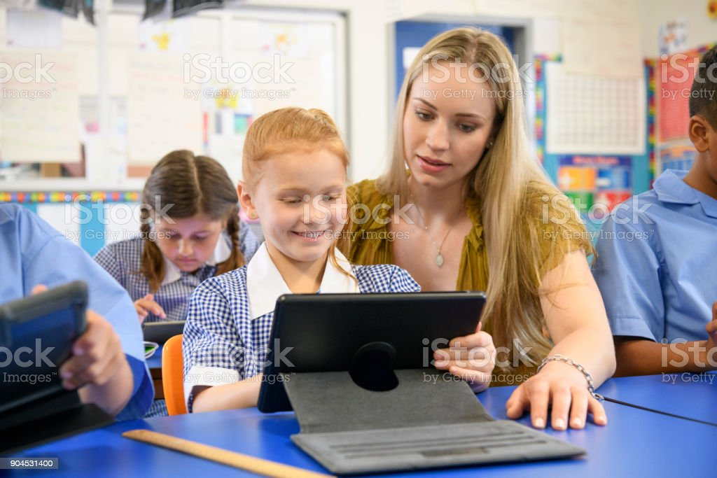 Teacher helping young girl using digital tablet in classroom stock photo