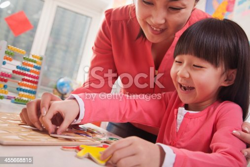 istock Teacher Helping Young Girl with Cut-Out Alphabet Letters 455668815