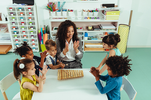 Teacher and children playing with musical toys in kindergarten