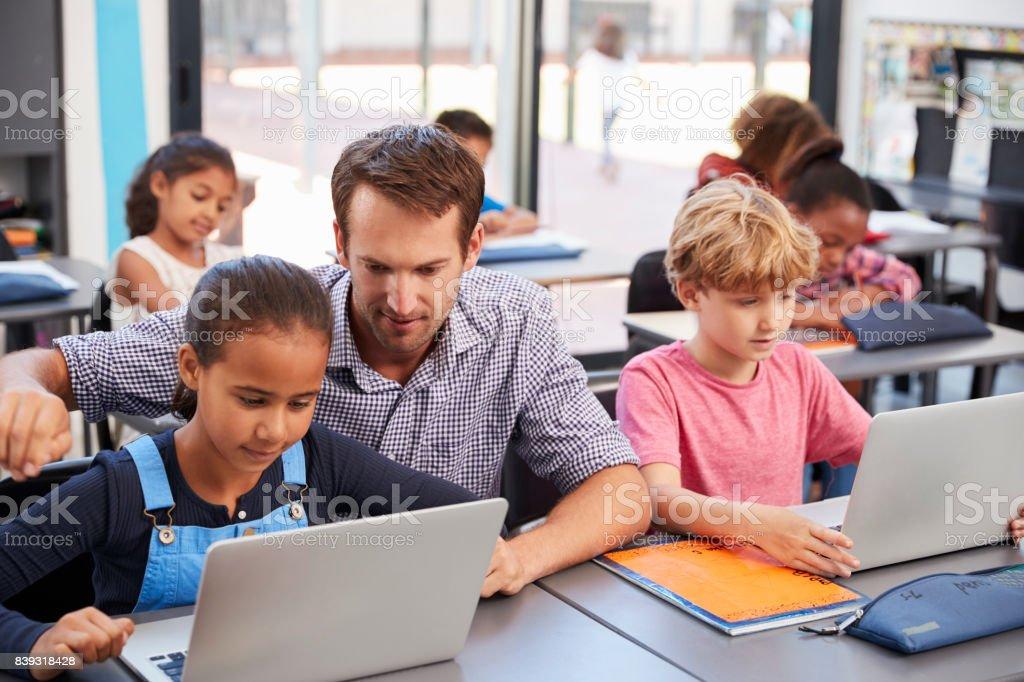 Profesor ayudar a los jóvenes estudiantes con ordenadores portátiles de clase - foto de stock