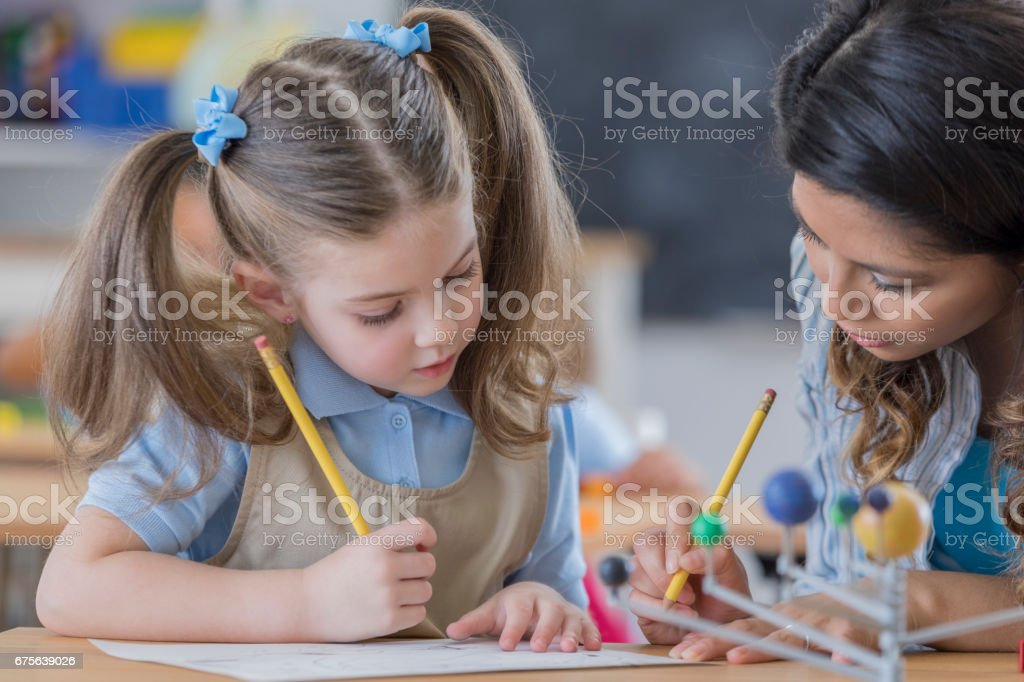 Teacher helps student during science class royalty-free stock photo