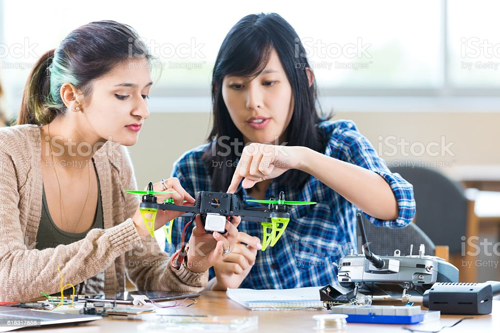Teacher helps student with drone in STEM high school stock photo