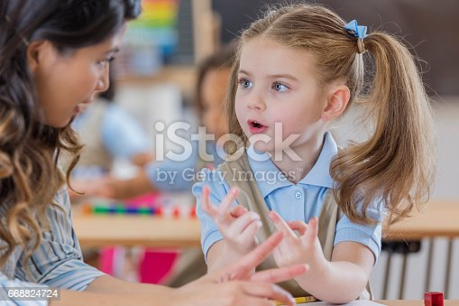 Caring teacher helps a young schoolgirl with math assignment. The girl is counting on her fingers.