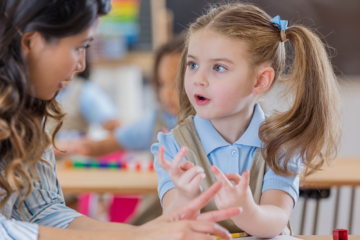istock Teacher helps young student with math 668824724
