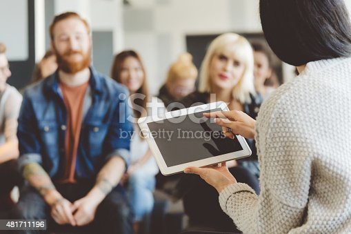 istock Teacher holding a digital tablet against auditorium 481711196