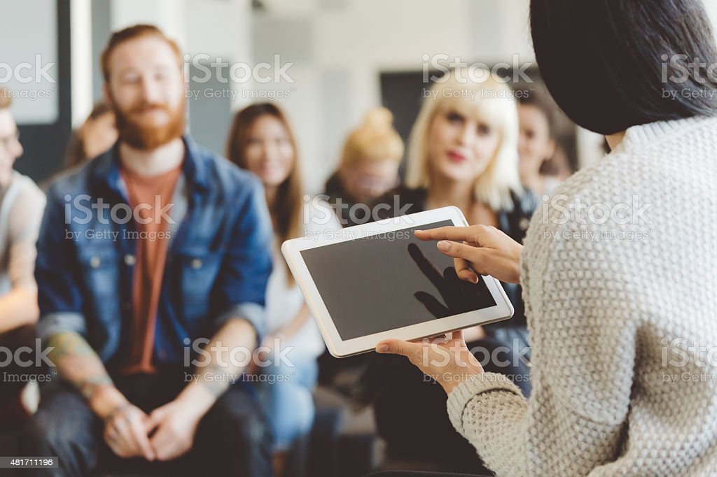 Teacher holding a digital tablet against auditorium stock photo