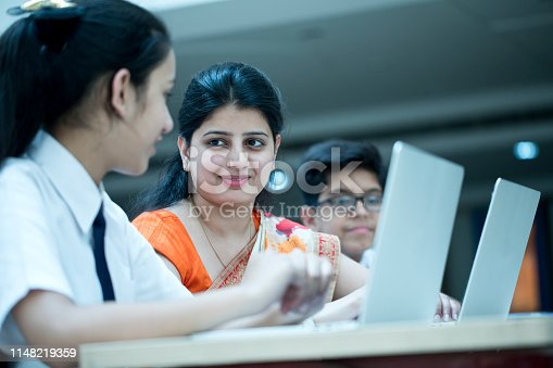 Teacher holding digital tablet while teaching students in classroom