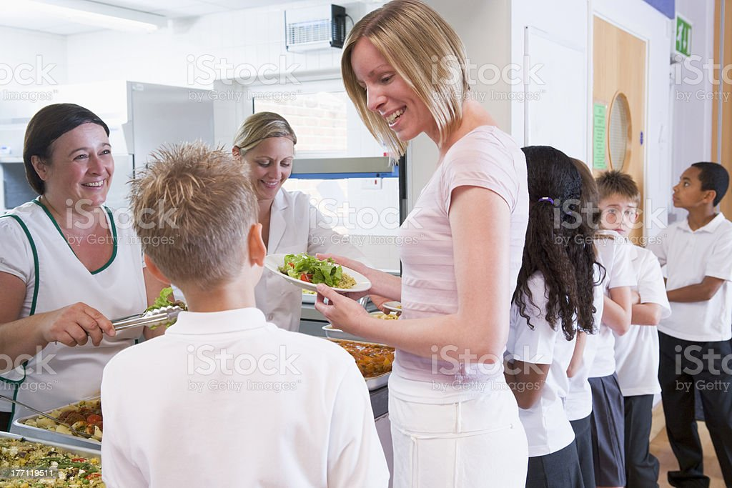 Teacher holding plate of lunch in school cafeteria stock photo