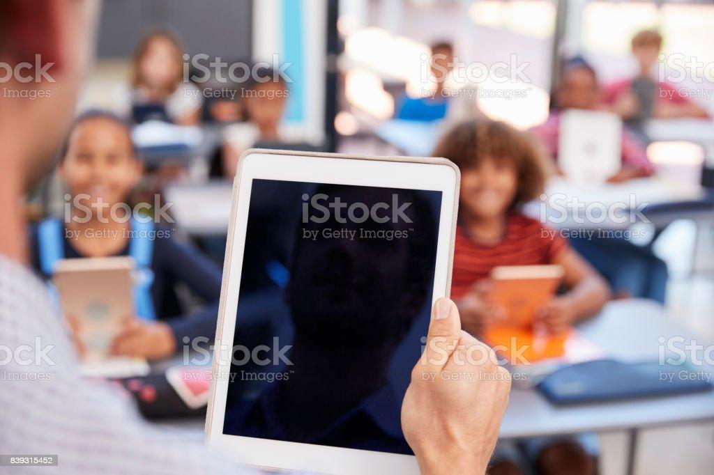 Tablet de exploração de professor na classe de escola, sobre a exibição de ombro - foto de acervo